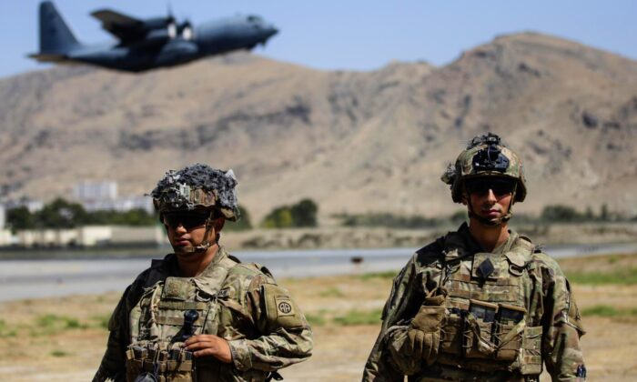 Two paratroopers assigned to the 1st Brigade Combat Team, 82nd Airborne Division conduct security while a C-130 Hercules takes off during a evacuation operation in Kabul, Afghanistan on Aug. 25, 2021. (Department of Defense via AP)