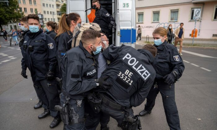 Police restrain a demonstrator, during a protest against coronavirus restrictions, in Berlin, on Aug. 28, 2021. (Christophe Gateau/dpa via AP)