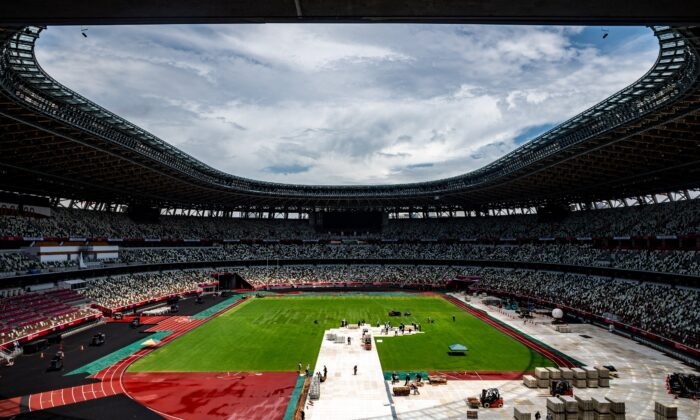 This general view shows the Olympic Stadium as staff members clear up in Tokyo on Aug. 9, 2021, the morning after the closing ceremony for the 2020 Tokyo Olympic Games. (Philip Fong/AFP via Getty Images)