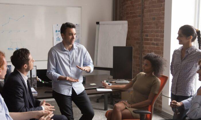 Co-workers socializing in the office. (Shutterstock)