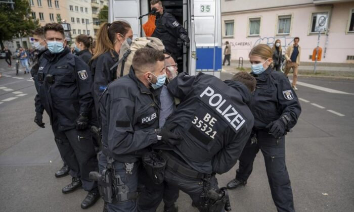 Police restrain a demonstrator during a protest against coronavirus restrictions in Berlin, Aug. 28, 2021. (Christophe Gateau/dpa via AP)