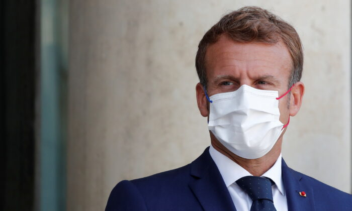 French President Emmanuel Macron, wearing a protective face mask, waits for the arrival of Madagascar's President Andry Rajoelina (not seen) at the Elysee Palace in Paris, France, on Aug. 27, 2021. (Benoit Tessier/Reuters)
