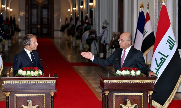 Iraqi President Barham Salih, right, and French President Emmanuel Macron attend a press conference, in Baghdad's Presidential Palace, Iraq, on Aug. 28, 2021. (Khalid Mohammed/AP Photo)