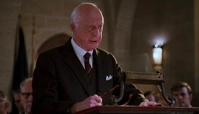 man in dark suit stands at podium in Dead Poets Society
