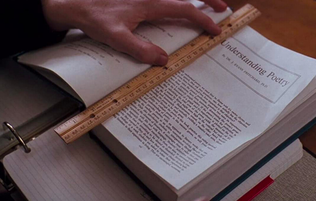 hand holding a ruler on top of a book in Dead Poets Society