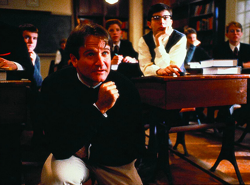 man kneels in high school classroom in Dead Poets Society