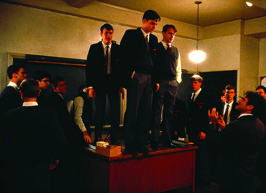 three boys stand on a desk in Dead Poets Society