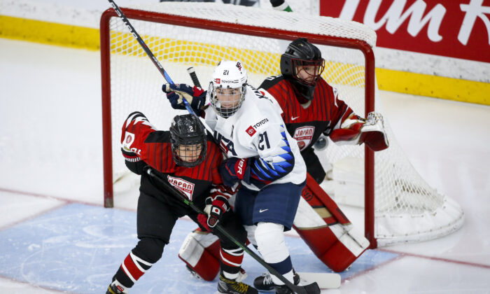 Hilary Knight, centrer, of the United States, tries to hold her position as Japan's Shiori Koike checks in front of Japan goalie Nana Fujimoto during second-period quarterfinal IIHF women's world championship hockey game action in Calgary, Alberta, on Aug. 28, 2021. (Jeff McIntosh/The Canadian Press via AP)