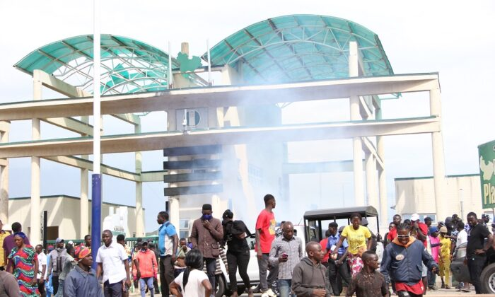 Police fire teargas to disperse protesters at the Government House in Jos, Nigeria, on Aug. 25, 2021. (Masara Kim/The Epoch Times)