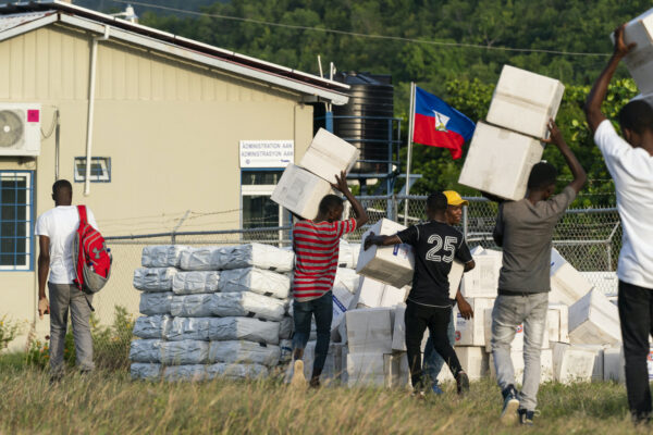 Haitian aid workers move aid boxes