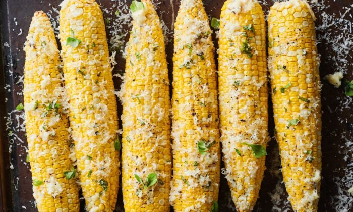 Sweet, slightly charred roasted corn is rubbed with Parmesan-garlic butter and showered with more Parmesan and fresh basil. (Joe Lingeman/TNS)