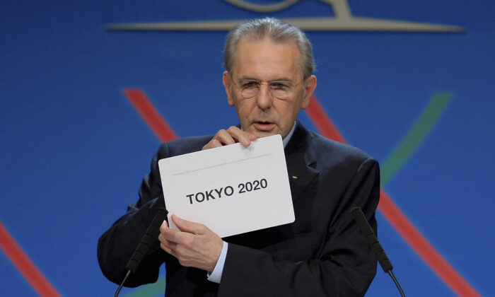 International Olympic Committee (IOC) President Jacques Rogge shows the name of the city of Tokyo elected to host the 2020 Summer Olympics in Buenos Aires, Argentina on Sept. 7, 2013. (Fabrice Coffrini/Pool photo via AP)