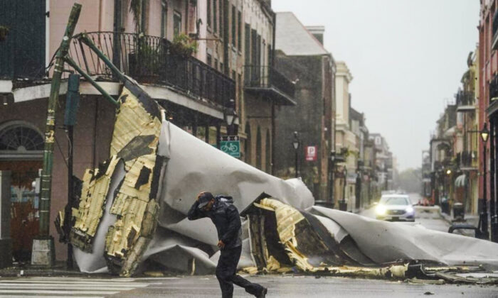 A man passes by a section of roof that was blown off of a building in the French Quarter by Hurricane Ida winds, in New Orleans, La., on Aug. 29, 2021. (Eric Gay/AP Photo)