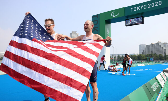 Brad Snyder and guide Greg Billington of Team United States react as they cross the finish line to win the gold medal during the men's PTVI Triathlon on day 4 of the Tokyo 2020 Paralympic Games at Odaiba Marine Park on Aug. 28, 2021 in Tokyo, Japan. (Lintao Zhang/Getty Images)