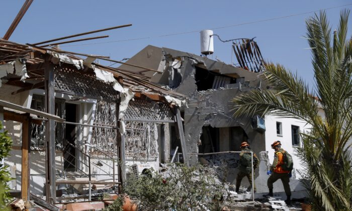 Israeli soldiers inspect homes destroyed by a missile fired from the Gaza Strip in the southern Israeli city of Ashkelon on May 11, 2021. (AP Photo/Ariel Schalit)