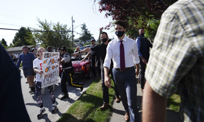 A protester yells at Liberal Leader Justin Trudeau as he makes his way to a motorcade in Surrey, B.C., on Aug 25, 2021. (Sean Kilpatrick/The Canadian Press)
