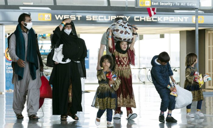 A family evacuated from Kabul, Afghanistan walks through the terminal at Washington Dulles International Airport in Chantilly, Va., on Aug. 30, 2021. (AP Photo/Jose Luis Magana)