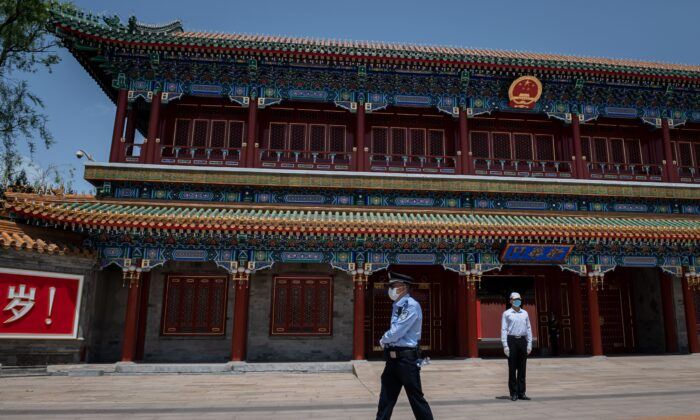 A security guard (right) and a police officer (left) secure the area at the entrance to the Zhongnanhai leadership compound in Beijing on May 18, 2020. (Nicolas Asfouri/AFP via Getty Images)
