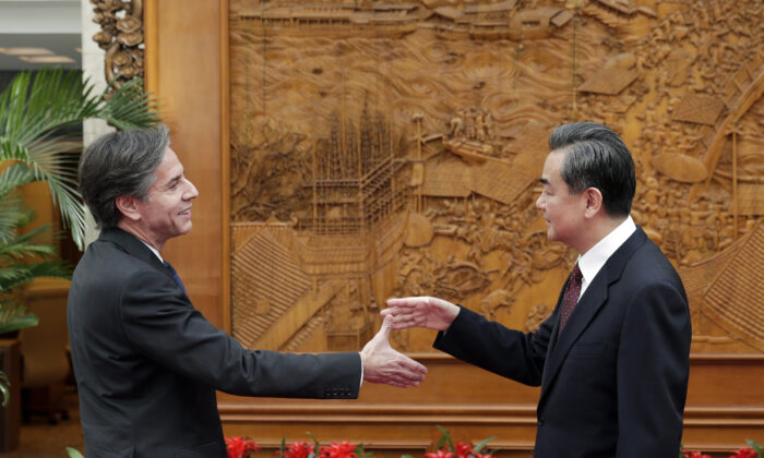 Antony Blinken, who was then-U.S. Deputy Secretary of State (L), shakes hand with China's foreign minister Wang Yi at the Olive Hall before a meeting at the Chinese Foreign Ministry office in Beijing on Feb. 11, 2015. (Andy Wong-Pool/Getty Images)