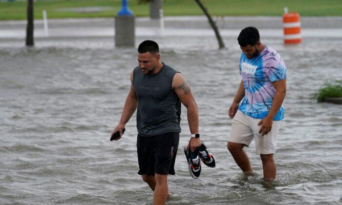 People walk through flooded streets near Lake Pontchartrain as Hurricane Ida nears, in New Orleans, La., on Aug. 29, 2021. (Gerald Herbert/AP Photo)