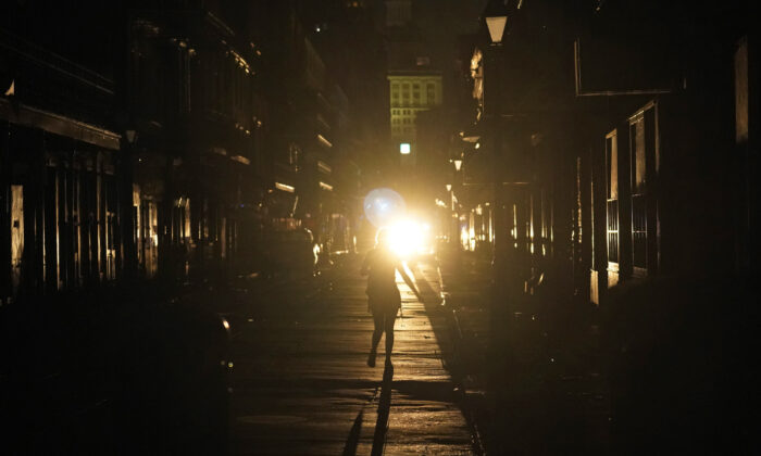 A police officer patrols past woman walking along Bourbon Street in the French Quarter after Hurricane Ida knocked out power to the city, in New Orleans, La., on Aug. 30, 2021. (Eric Gay/AP Photo)