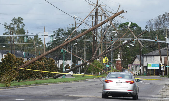 Traffic diverts around power poles that hang over a road after Hurricane Ida moved through Metairie, La., on Aug. 30, 2021. (Steve Helber/AP Photo)