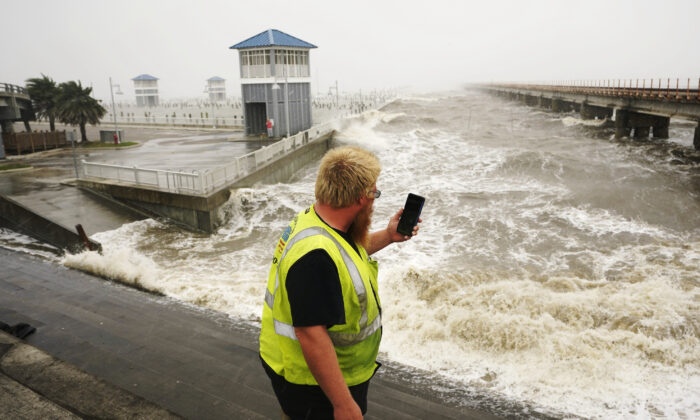 A utility worker photographs waves as they slam against a sea wall at the city marina as outer bands of Hurricane Ida arrive in Bay Saint Louis, Miss., on Aug. 29, 2021. (AP Photo/Steve Helber)