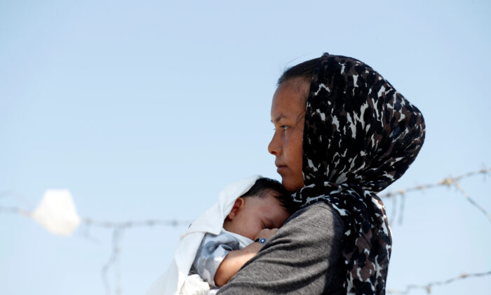 An Afghan woman and her month-old son are seen outside the new temporary camp for illegal immigrants and refugees, on the island of Lesbos in Greece, on Sept. 21, 2020. (Yara Nardi/Reuters)