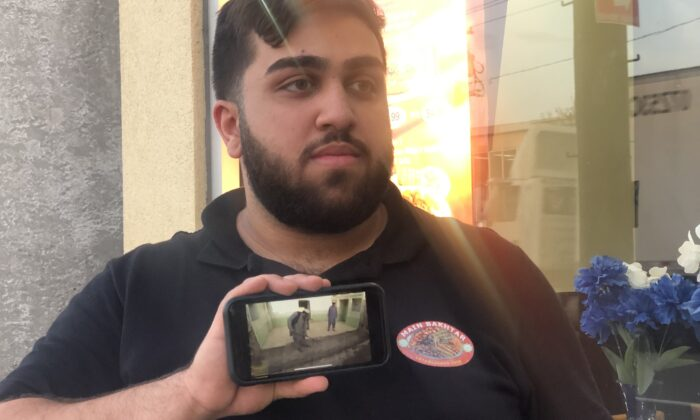 Karim Faizy, manager of Bakhtar Halal Kabab, in Hicksville, Long Island, shows a video of his uncle cleaning up his house after it was bombed in Afghanistan, on Aug. 30, 2021. (Enrico Trigoso/The Epoch Times)