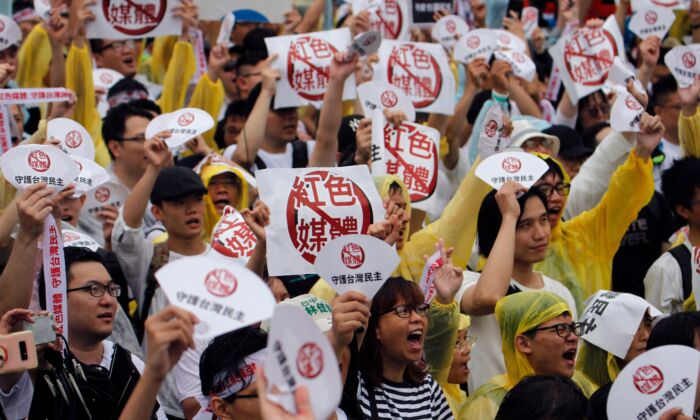 """Protesters hold placards with messages that read """"reject red media"""" and """"safeguard the nation's democracy"""" during a rally against pro-China media in Taipei on June 23, 2019. (Hsu Tsun-hsu / AFP)"""