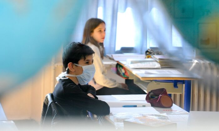 A pupil wearing a face mask attends a class  in a file photo. (JEAN-CHRISTOPHE VERHAEGEN/AFP via Getty Images)