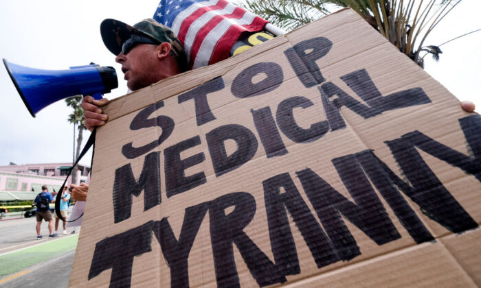 A protester holds a sign and a flag as he takes part in a rally against COVID-19 vaccine mandates, in Santa Monica, Calif., on Aug. 29, 2021. (Ringo Chiu/AFP via Getty Images)