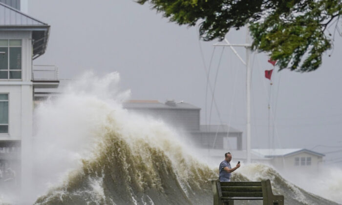 A man takes pictures of high waves along the shore of Lake Pontchartrain as Hurricane Ida nears, in New Orleans, La., on Aug. 29, 2021. (Gerald Herbert/AP Photo)