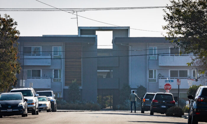 A man stand by his car in front of his home facing an apartment complex in Newport Beach, Calif.,on Jan. 8, 2021. (John Fredricks/The Epoch Times)