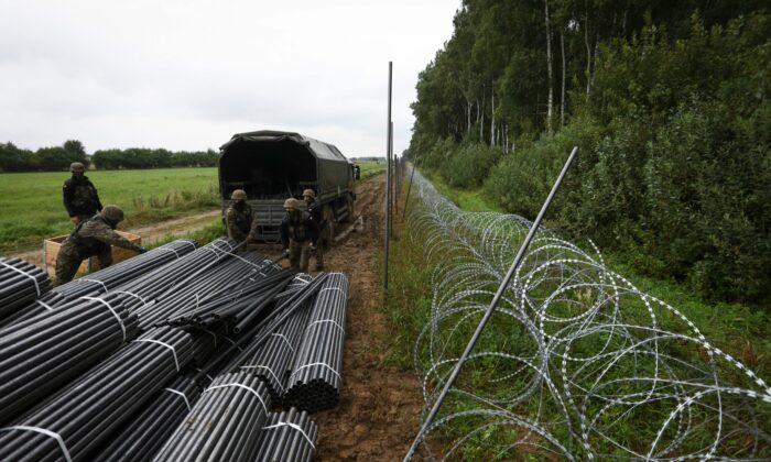 Polish soldiers unload materials to construct a barbed wire fence on the border with Belarus in Zubrzyca Wielka near Bialystok, eastern Poland on Aug. 26, 2021. (Jaap Arriens/AFP via Getty Images)