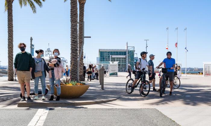 People walk along the sidewalks near the Port of San Deigo, Calif., on March 27, 2021. (John Fredricks/The Epoch Times)