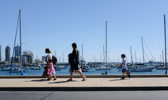 People walk along the sidewalks near the Port of San Diego, Calif., on March 27, 2021. (John Fredricks/The Epoch Times)