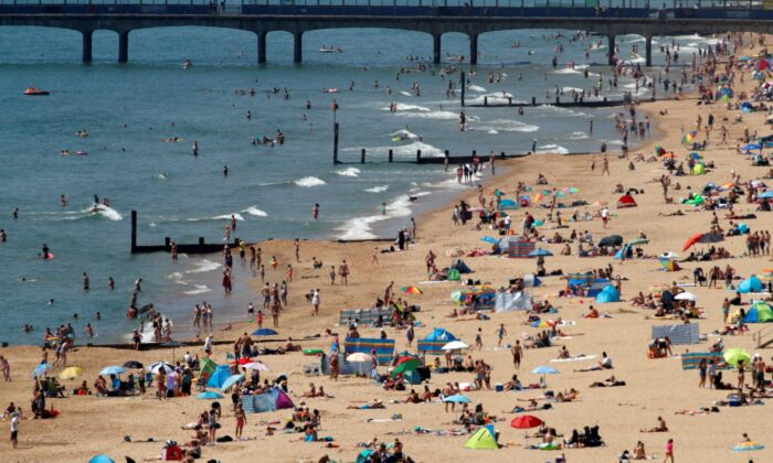 Sunbathers enoy the warm weather on the beach near Boscombe Pier in Bournemouth, south England on May 30, 2020. (Adrian Dennis/AFP via Getty Images)