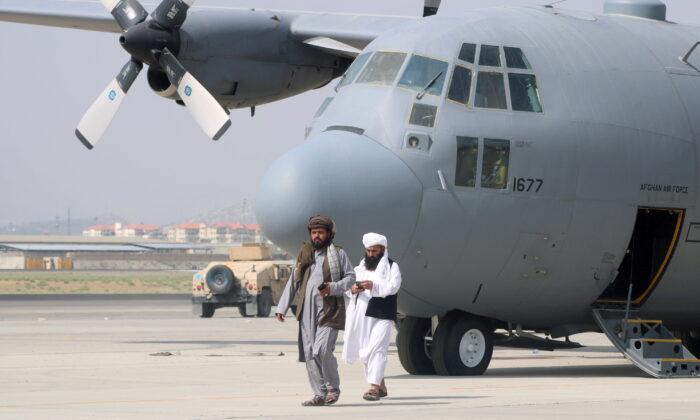 Taliban terrorists walk in front of a military airplane a day after the U.S. troop withdrawal from Hamid Karzai International Airport in Kabul, Afghanistan, on Aug. 31, 2021. (Stringer/Reuters)