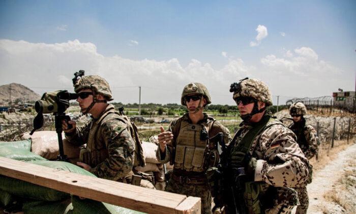 U.S. Marines and a German service member watch an entry gate during an evacuation at Hamid Karzai International Airport, Kabul, Afghanistan, on Aug. 28, 2021. (U.S. Marine Corps/Cpl. Davis Harris/Handout via Reuters)
