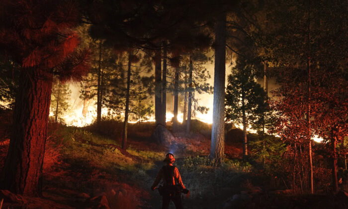 A firefighter monitors the Caldor Fire burning near homes in South Lake Tahoe, Calif., on Aug. 30, 2021. (Jae C. Hong/AP Photo)