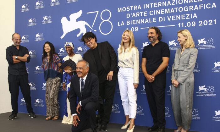 Jury members Alexander Nanau, from left, Chloe Zhao, Cynthia Erivo, Jury president Bong Joon Ho, Virginie Efira, Saverio Costanzo, Sarah Gadon, and director of the Venice Film festival Alberto Barbera, front, pose for photographers at the photo call for the jury during the 78th edition of the Venice Film Festival in Venice, Italy, on Sept. 1, 2021. (Joel C Ryan/Invision/AP)