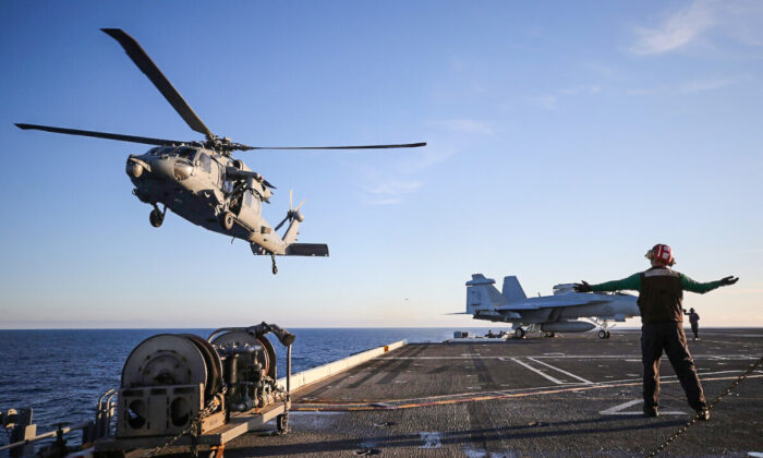 A U.S. Navy MH-60S helicopter descends to land on the flight deck of the USS Nimitz aircraft carrier while at sea off the coast of Baja California, Mexico, on Jan. 18, 2020. (Mario Tama/Getty Images)
