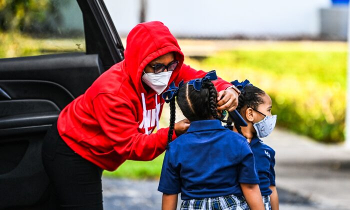 A mother adjusts the facemask of her child as she enters the St. Lawrence Catholic School on the first day of school after summer vacation in north of Miami on Aug. 18, 2021. (Chandan Khanna/AFP via Getty Images)