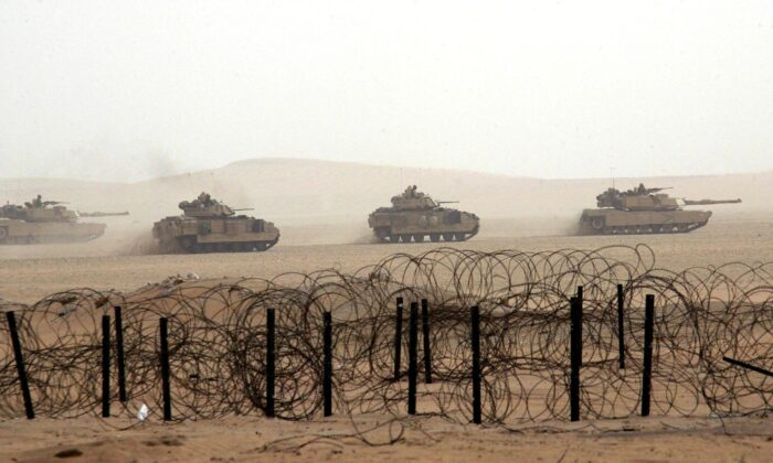 U.S. army tanks roll through the Kuwaiti desert during maneuvers, some 15 miles from the Iraqi border, Dec. 21, 2002. (Rabih Moghrabi/AFP via Getty Images)