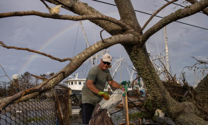 A rainbow is seen in the background as Jody Galliano clears debris from his yard in the aftermath of Hurricane Ida in Galliano, La., on Aug. 31, 2021. (Adrees Latif/Reuters)