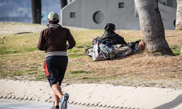 A jogger runs past a homeless man in Venice Beach, Calif., on Jan. 27, 2021. (John Fredricks/The Epoch Times)