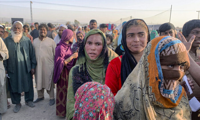 Afghan families gather to receive food stuff distributing by an Islamabad-based Christian organization on the outskirts of Chaman, a town in the Pakistan's southwestern Baluchistan province, on the border with Afghanistan, on Aug. 31, 2021. Dozens of Afghan families have crossed into Pakistan through the southwestern Chaman border a day after the U.S. wrapped up its 20-year military presence in the Taliban-controlled country. (AP Photo)