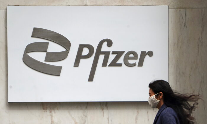 A person walks past a Pfizer logo amid the COVID-19 pandemic in the Manhattan borough of New York City, New York on April 1, 2021. (Carlo Allegri/Reuters)
