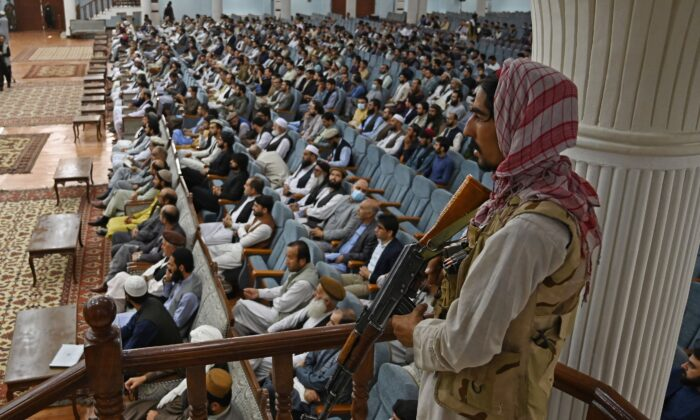 A Taliban fighter stands guard as the group's Higher Education Minister Abdul Baqi Haqqani speaks on the Taliban's higher education policies at the Loya Jirga Hall in Kabul on Aug. 29, 2021. Afghan women will be allowed to study at university but there will be a ban on mixed classes under Taliban rule, Haqqani said. (Aamir Qureshi/AFP via Getty Images)